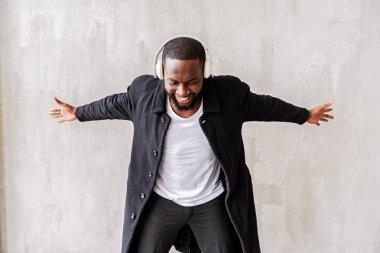 Jolly handsome african man with beard enjoying his beloved songs via earphones