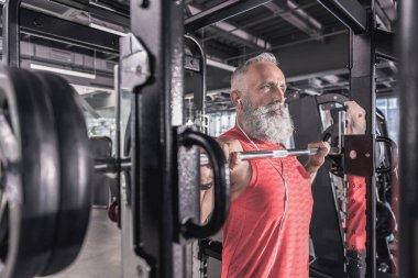 Confident senior man is doing sport in modern gym