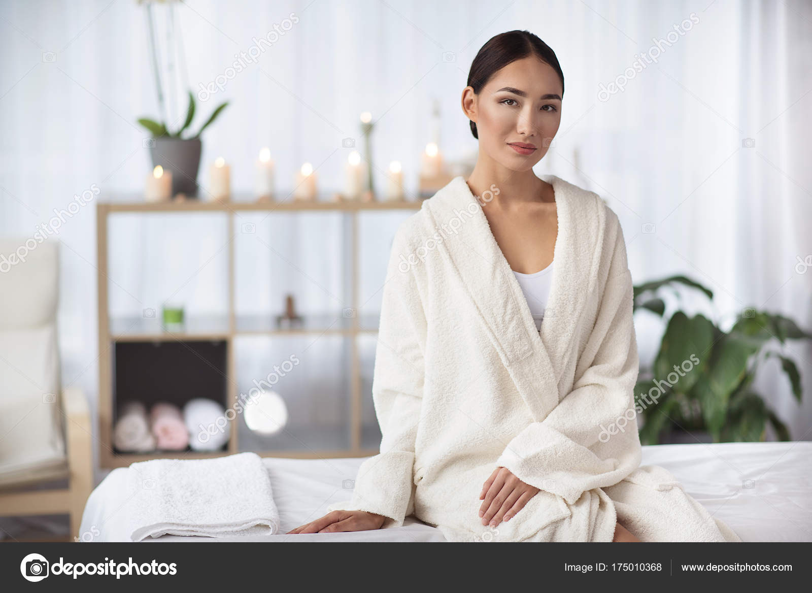 Portrait of elegant relaxed young asian woman in white bathrobe is sitting  on massage table at spa salon with candles in background. 51ae08df2