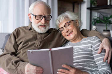 Charming senior couple relaxing on sofa with book