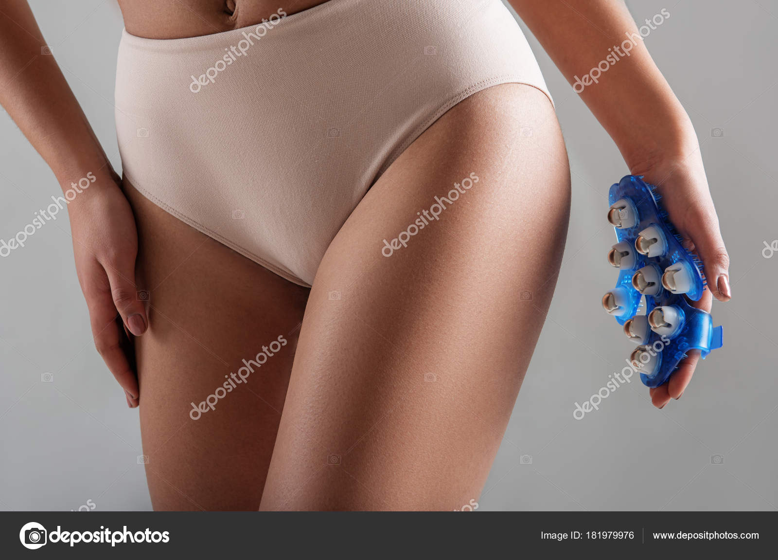 Close Up Of Female Hand Holding Hand Massager Close To Backsides Woman Is Taking Care Of Her Slender Body Isolated On Background Photo By