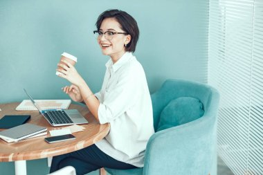 Happy lady is enjoying hot drink at workplace