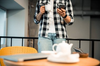 Young man holding cup of tea and mobile phone in cafe