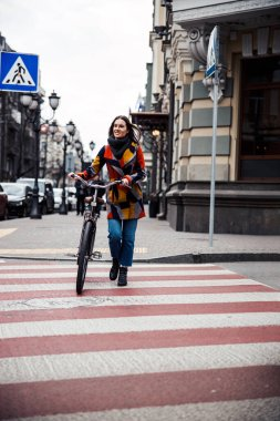 Mirthful cycler walking on crossroad and smiling stock photo