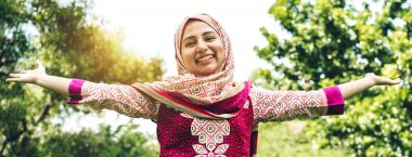Portrait of happy beautiful asian arabic muslim woman with hijab dress relaxing standing stretch her arms relax and enjoy with nature fresh air in green park background