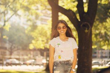 Woman in sunglasses over sunbeams
