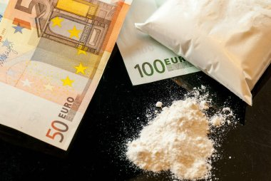 euro bills and cocaine drugs traffic addiction concept