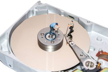 Miniature people repairing the hard drive. A broken computer equipment.
