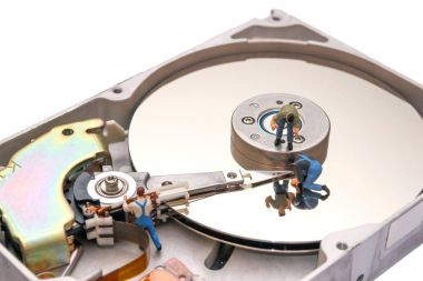 Creative concept with miniature people. Workers repairing the hard drive.