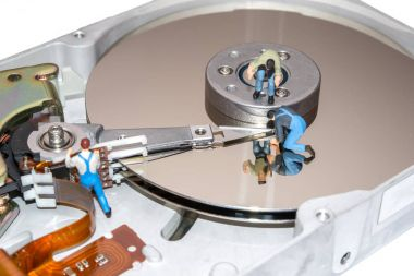 Creative concept with miniature people. Workers repairing the hard drive