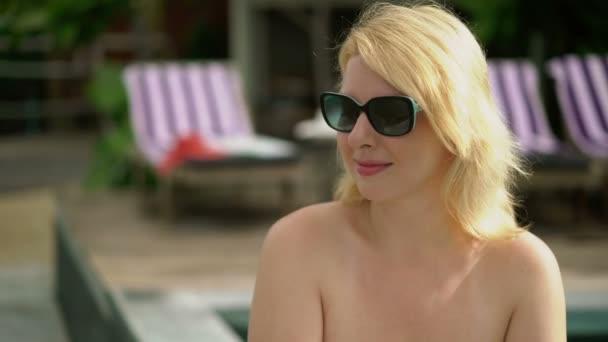 Young woman suntanning near pool