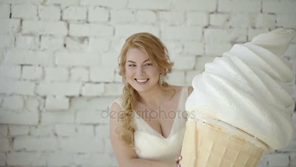 Roztomilá mladá blondýnka ve svatebních šatech pózuje ve studiu s obrovský Zmrzlinový pohár