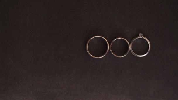 Three wedding rings on dark background