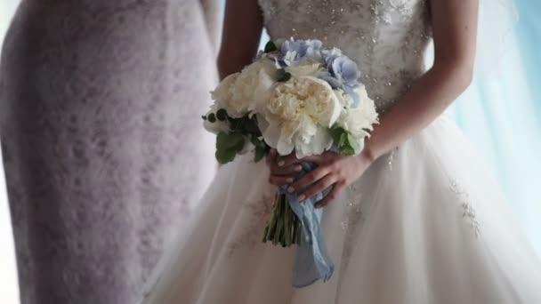 nevěsta drží svatební květiny