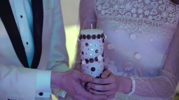 Nevěsta a ženich drží svíčku