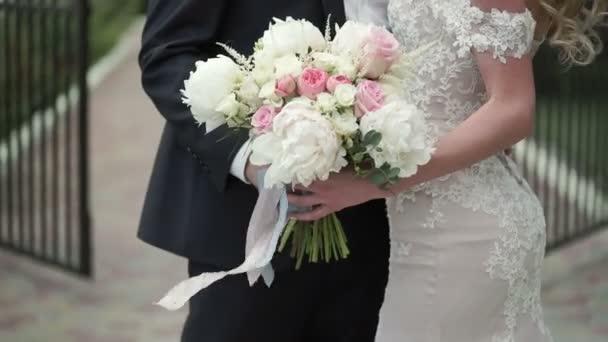 Braut und Bräutigam mit Blumenstrauß