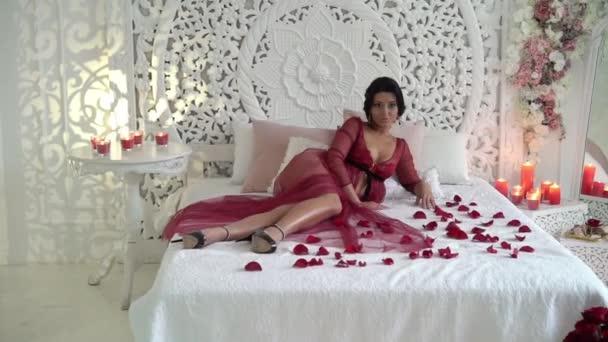 Giovane donna bruna in lingerie rossa in posa