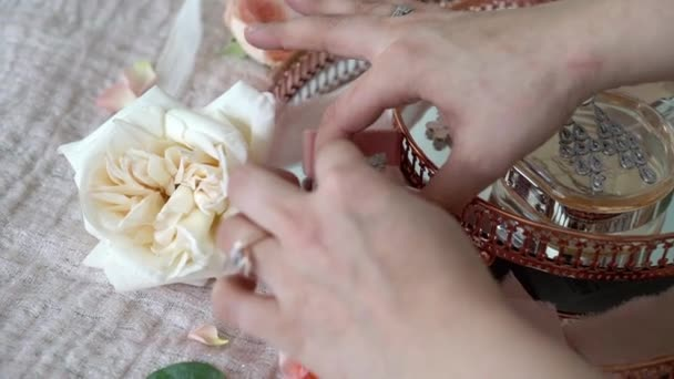 Woman put jewelry ring in a box at pink tray with bridal earrings proposal ring and perfume