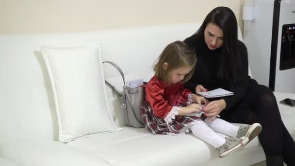 Matka a malou dcerou sledování knihy se samolepkami