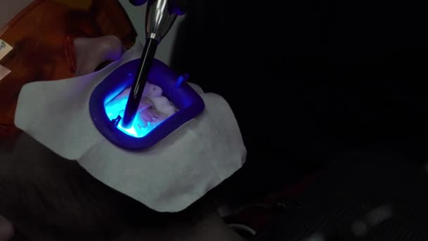 Dentist whitening teeth for patient with uv lamp