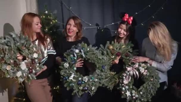 Felkészülés a karácsony és az újév ünneplésére. Lányok díszített fenyőkoszorúval golyókkal és játékokkal. Ünnepi hangulat