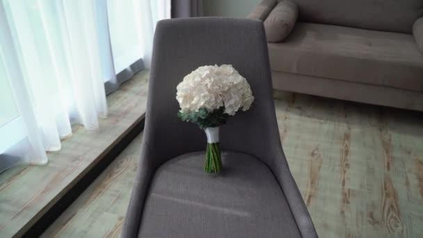 Kytice z bílých hortenzií. Svatební kytice nevěsty. Ranní přípravy novomanželů. Květinové uspořádání na židli v ložnici