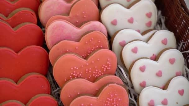 Piros, rózsaszín és fehér sütik szív alakban sütve.