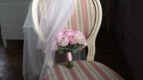 Kytice z růžových růží. Svatební kytice nevěsty. Ranní přípravy novomanželů. Květinové aranžmá na židli v ložnici - květiny a závoj.