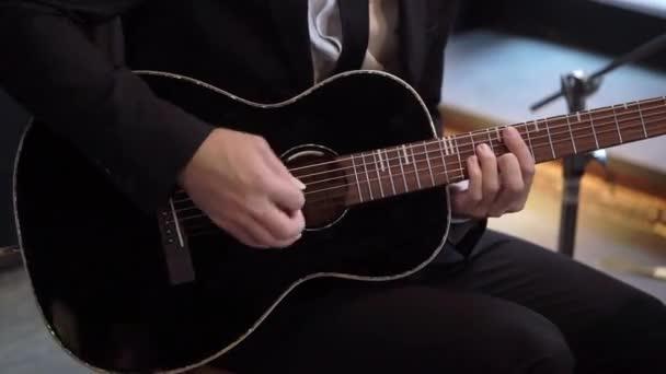 Kytarista hraje na kytaru na koncertě. Hudebník s smyčcovým nástrojem na pódiu.