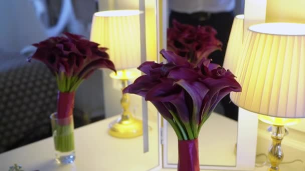 Bouquet of flowers of violet purple callas. Wedding bouquet of the bride. Morning preparations of the newlyweds. Floral arrangement on a table near mirror in the bedroom
