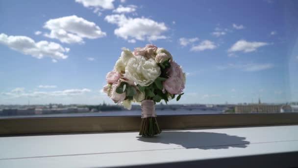 Kytice květů bílých a růžových pivoňek u okna. Svatební kytice nevěsty. Ranní přípravy novomanželů.