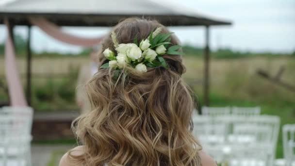 A menyasszony eljön a vőlegényéhez az esküvői ceremónián. Első találkozás a szabadban oltár közelében a parkban.
