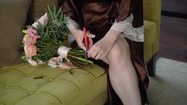 Mladá žena krájí růže nůžkami. Prořezávání červených květin