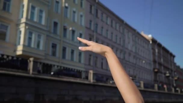Mladá žena plující lodí nebo jachtou ve městě. Zvedá a mává rukou