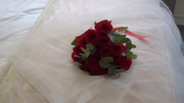 Kytice z červených růží. Svatební kytice nevěsty. Ranní přípravy novomanželů. Květinové aranžmá na posteli v ložnici - květiny a závoj.
