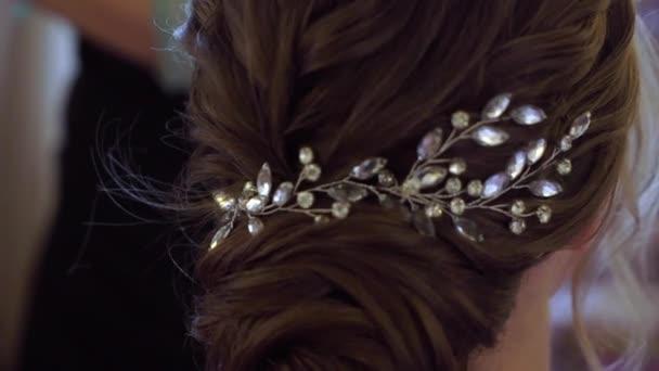 Šperky ve vlasech, zdobení účesu pro ženy. Kadeřník pracující s brunetkou nevěstou na svatbě