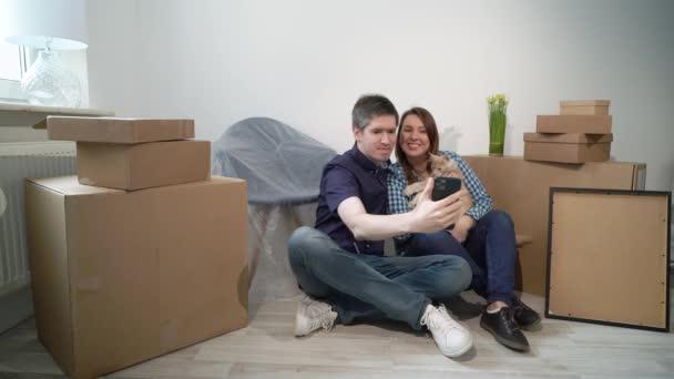 Junges Paar mit Katze macht Selfie mit Handy. Umzug in neue Wohnung