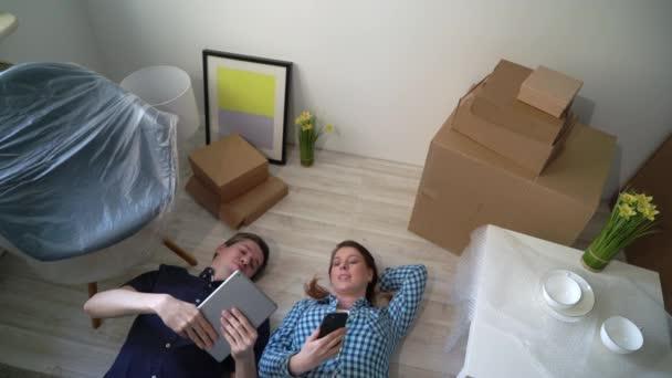 Junges Paar liegt am Boden und entspannt sich in der Wohnung. Umzug in eine neue Heimat