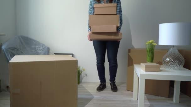Umzug in ein neues Zuhause. Frau öffnet Karton, Wohnungseigentümer
