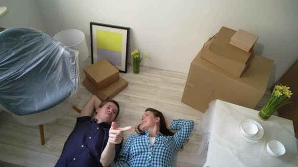Young couple laying at the floor and relaxing in apartment. Moving to new home