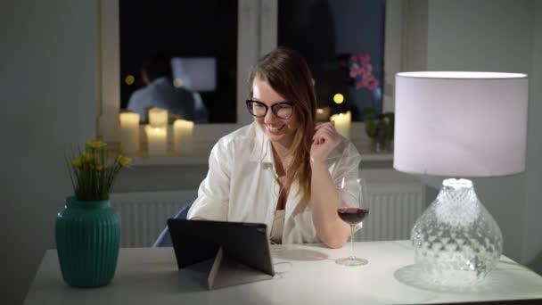 Junge Frau arbeitet am Tablet-Laptop zu Hause Abend mit Wein, Videoanruf