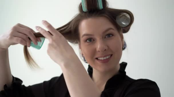 Dívka používá kadeřníka na vlasy, dělá účes. Mladá žena v županu prádlo.