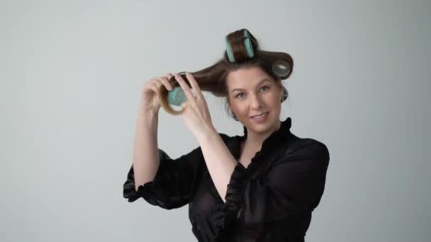 Mädchen mit Lockenwickler auf Haar, macht Frisur. Junge Frau in Bademantel-Unterwäsche.
