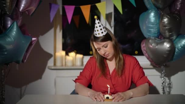 Junge Frau feiert ihren Geburtstag allein. Traurig gelangweilt und müde Mädchen bday
