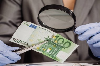 policewoman with magnifying glass checks suspicious money
