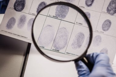 Detective through a magnifying glass looking at a fingerprint