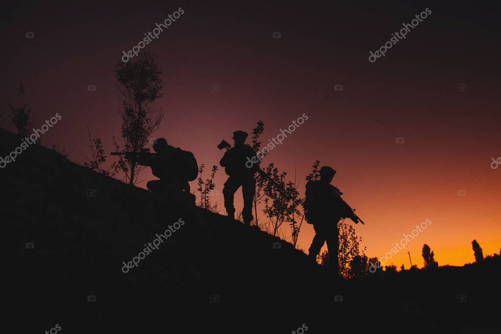 Silhouette of military soldiers with weapons at night