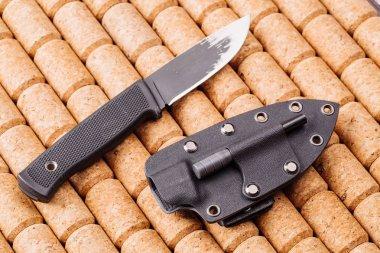 Black knife on wooden background.