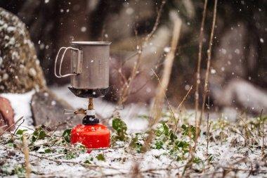 titanium mug on gas burner in forest