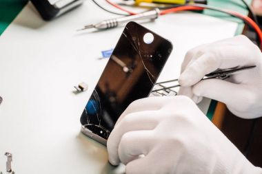Close up hands of a service worker repairing modern smarphone.